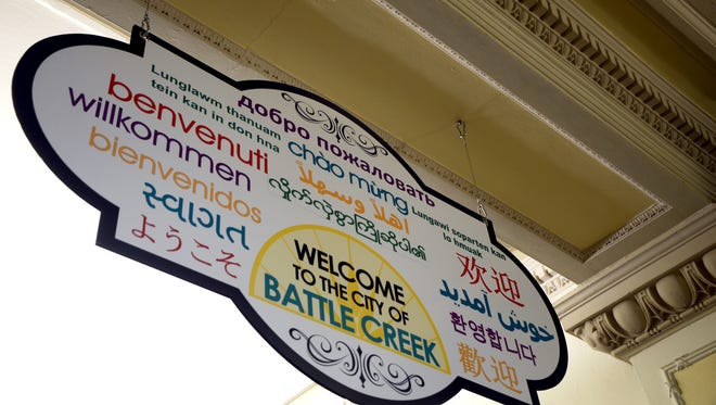 A sign welcoming visitors in multiple languages hangs on the first floor of Battle Creek City Hall. The signs were installed after the city signed onto the Welcoming Michigan program.