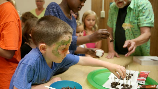 """Dominic Downing, 5, reaches for a power bar bite made with crickets at Kitsap Regional Library's """" The Bug Chef """" presentation at the Sylvan Way branch. Kids were offered bugs snacks by bug chef David George Gordon."""