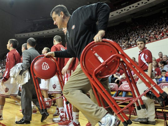 San Francisco 49ers head football coach Jim Harbaugh hustles as he carries chairs onto the floor for an Indiana time out as the Indiana Hoosiers defeated the North Carolina Central Eagles 75-56 at Assembly Hall in Bloomington Wednesday February 22, 2012.  Joe Vitti / The Star