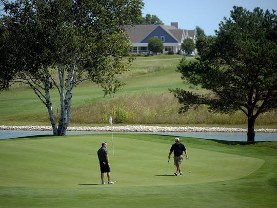 Golfers prepare their putts on hole No. 17 on Aug. 12 at The Orchards at Egg Harbor.