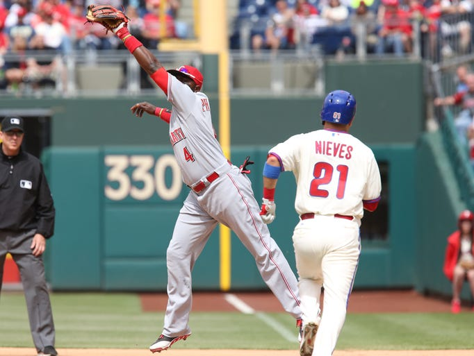 Cincinnati Reds second baseman Brandon Phillips (4) pulls in a high throw to tag out Philadelphia Phillies catcher Wil Nieves (21) in the fifth inning at Citizens Bank Park.