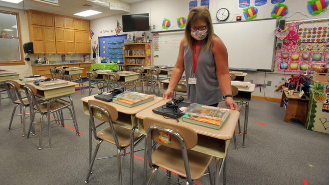 Allana Bryson arranges desks in her fourth grade classroom at Springmore Elementary School on Friday. Desk groups will be divided between cohort A and cohort B groups so that no student sits within six feet of a classmate.