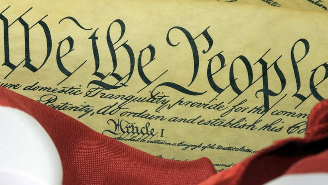 The U.S. Constitution is pictured with the American flag.