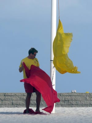 A Pensacola Beach lifeguard changes the the yellow flag for the red flag warning in this 2013 file photo. Red flag symbolizes no swimming in the Gulf, high surf and/or strong currents.