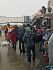 Airline passengers stand outside the terminal at Hartsfield-Jackson