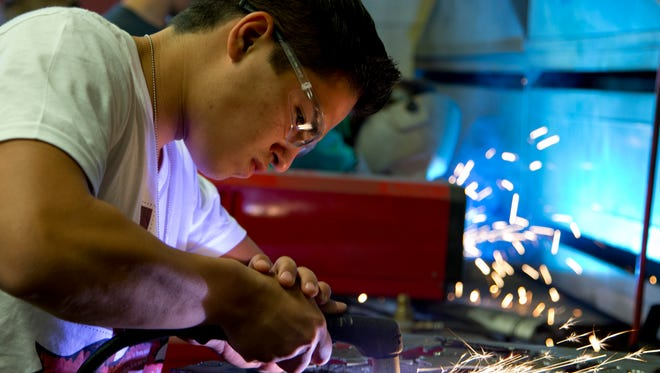 Anthony Garcia, 17, cuts a piece a mental during a welding foundations class at East Valley Institute of Technology's new Apache Junction campus at Apache Junction High on Thursday, March 27, 2014.