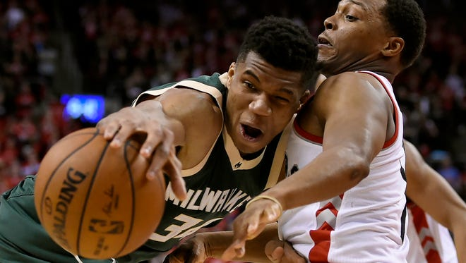 Toronto Raptors guard Kyle Lowry defends as Milwaukee Bucks forward Giannis Antetokounmpo tries to move the ball during the second half of Game 2 of their first-round playoff game Tuesday night in Toronto.