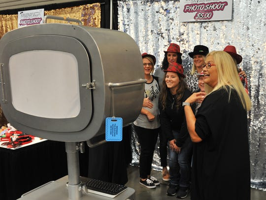 A group of friends pose for a photo in a photo booth Friday morning at the Ray Clymer Exhibit Hall during Christmas Magic.
