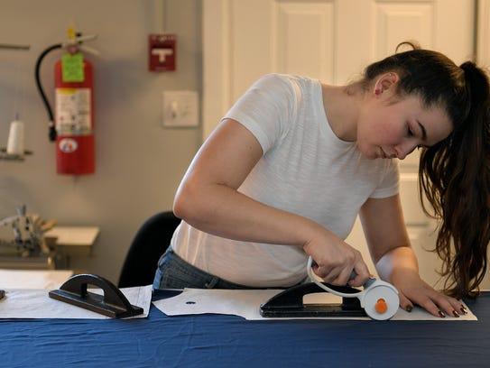 O'More College of Design junior Kelly Nieser cuts fabric