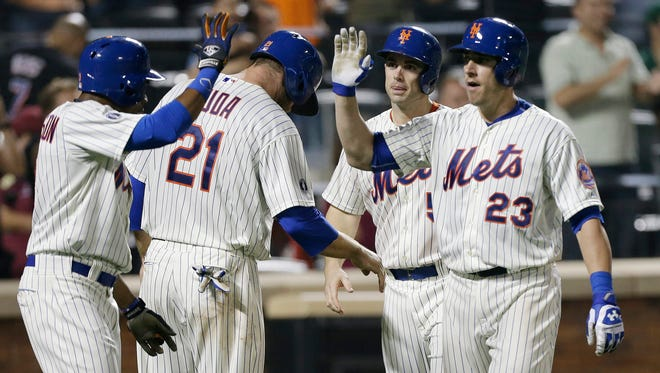 The Mets' Taylor Teagarden, right, celebrates with David Wright (5), Lucas Duda (21) and Curtis Granderson after hitting a grand slam during the sixth inning against Milwaukee on Tuesday.