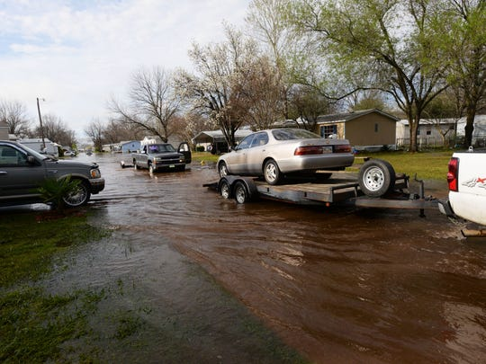 Residents tow their cars away from their homes in Pecan