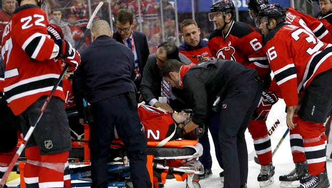 Trainers load Devils defenseman John Moore onto a stretcher to pull him off the ice after he was injured during the first period of a game against the Capitals on Saturday in Newark