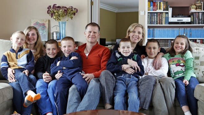 Bill and Stefanie Krebs with their children from left, Joseph, 7, Natalia, 20, William, 12, Patrick, 10, Nikolas, 7, Peter, 9, and Marta Mae, 10, are photographed, March 7, 2014 at their home in Valhalla. The Krebs adopted their seven children from the Ukraine.