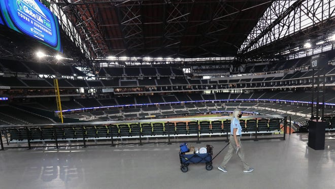 A Texas Rangers employee pulls a cart down an empty concourse at Globe Life Field, home of the Texas Rangers baseball team, in Arlington, Texas, Monday, June 1, 2020. It used to be that empty seats caused palpitations in team owners and college administrators relying on ticket sales and concessions to balance the budget. Now, those empty seats, and short lines and clear concourses, will be the norm for a while as sports grapples with social distancing requirements in the age of coronavirus.