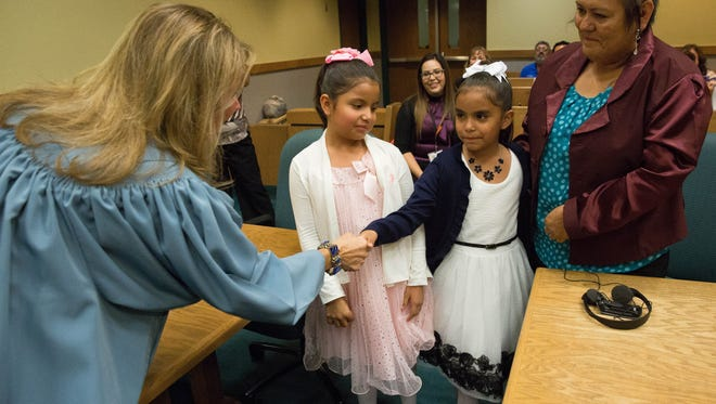 Joveigh Mendez,7, center, shakes hands with Judge Marci E. Beyer, after Joveigh and her twin sister Natalie Mendez,7, were officially adopted by Maria Mendez, right, at the Third Judicial District Court, Tuesday November 14, 2017.