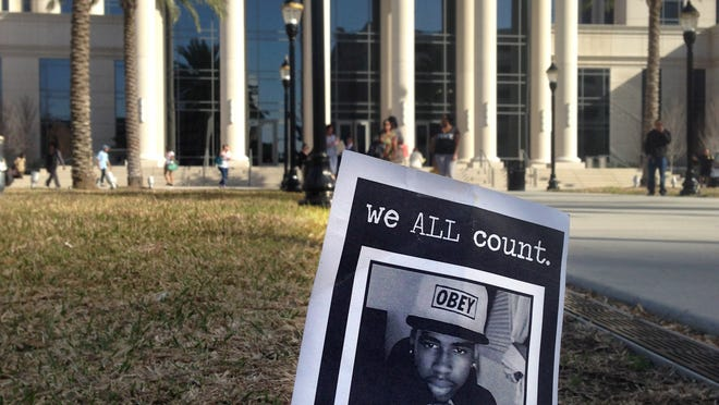 This Feb. 4, 2014 file photo shows a small memorial to Jordan Davis planted outside the courthouse in Jacksonville, Fla.