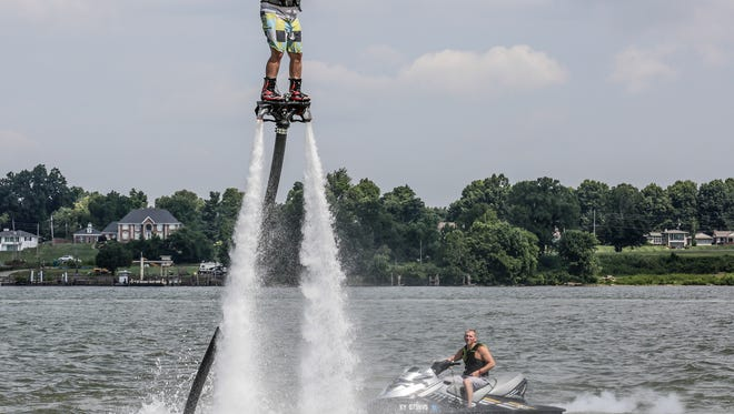 Russ Meredith hovers above the Ohio River on a column of water propelled by the personal watercraft operated by Mike Allen.June 21, 2016