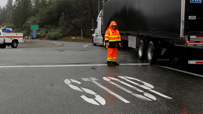 California Department of Transportation maintenance worker Toni Montini screens trucks for chains Friday at the Fawndale exit north of Redding.