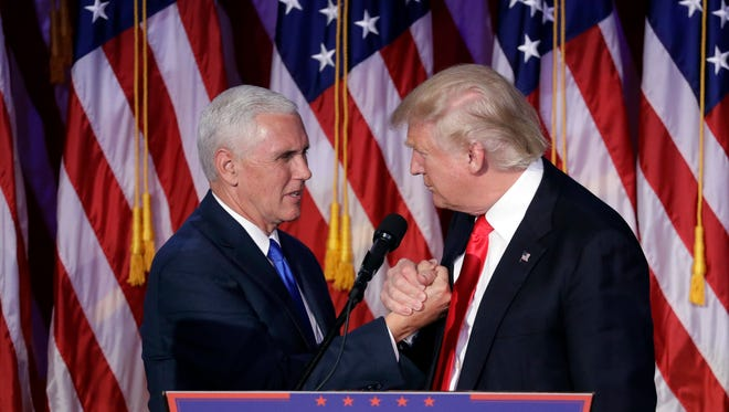President-elect Donald Trump shakes hands with Vice President-elect Mike Pence as he gives his acceptance speech during his election night rallyPhoto/John Locher)