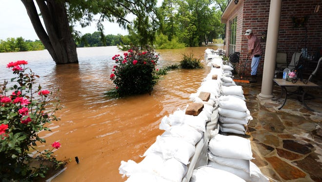 Kevin Parker sweeps water off the patio of his friends house in the Les Maisons Sur La Rouge subdivision where the only thing stopping water from coming into house is the sand bag wall.
