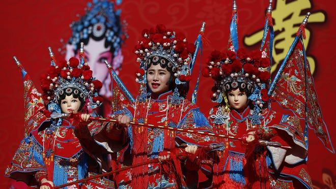 A Chinese dancer dressed in traditional costume perform a cultural dance on stage during a temple fair for a Lunar New Year celebration in Beijing, Monday, Feb. 8, 2016. Millions of Chinese began celebrating the Lunar New Year, which marks the Year of the Monkey on the Chinese zodiac.