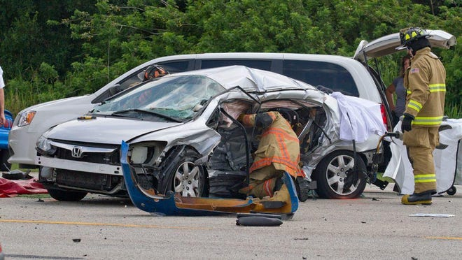 Firefighters work at the scene of a fatal multi-car crash on U.S. 41 in North Fort Myers on May 19. Going into the weekend, 116 people had died on Lee County roads.