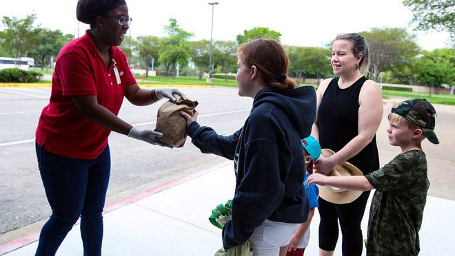 Tiffany Owens, marketing manager for the Round Rock school district food services department, hands meals to students Lola, Bodie and Wyatt, and their mother Lacy Grace in March. The school district will continue its curbside meal service through the end of July.