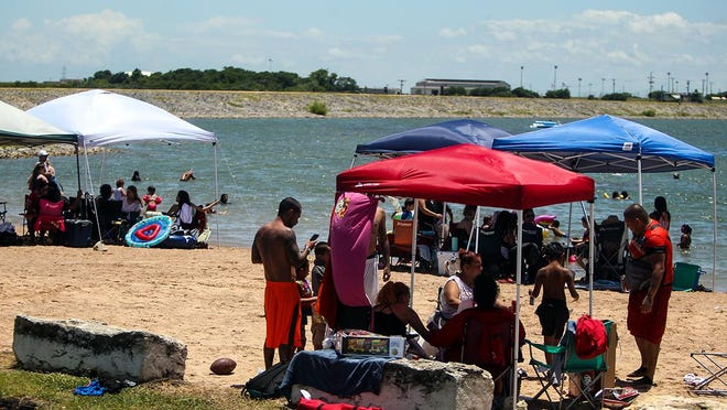 Crowds gather at Lake Pflugerville on Saturday. On June 16, the city opened the beach, playground, pavilion, boat ramp and fishing piers at the lake.