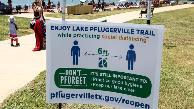 A sign at Lake Pflugerville reminds visitors to practice social distancing. Crowds gathered at lake on June 20.