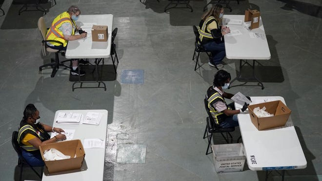 Workers at the Wake County Board of Elections, in Raleigh, prepare absentee ballots to be mailed to voters. In North Carolina, any registered voter may cast a mail-in ballot, but the ballot must be requested -- they are not sent out automatically.