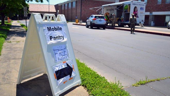 A sign advertising a Food Bank of Central and Northeast Missouri mobile pantry site sits in June outside Hickman High School. Retired teachers are starting a fundraising drive for the food bank.