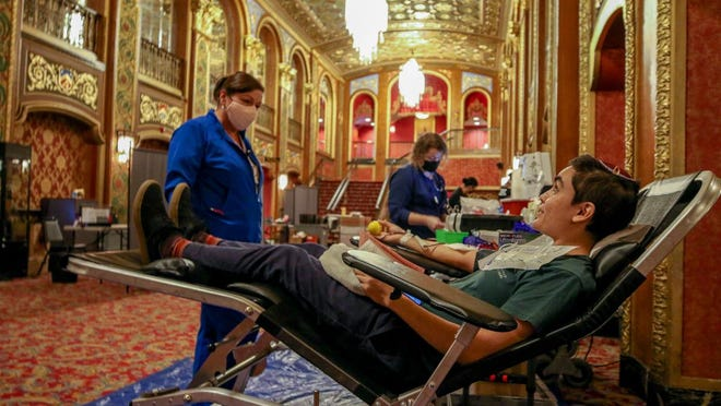 Deborah Zona, lead donor specialist at the Rhode Island Blood Center, chats with Brown University student and blood donor Akiva Chaleff in the opulent setting of the Providence Performing Arts Center lobby on Thursday. PPAC and WPRI 12, in partnership with the blood center, hosted a community blood drive.