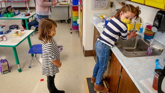 Cate Impey washes up after lunch as a classmate keeps socially distant at Hathaway Elementary School in Portsmouth.