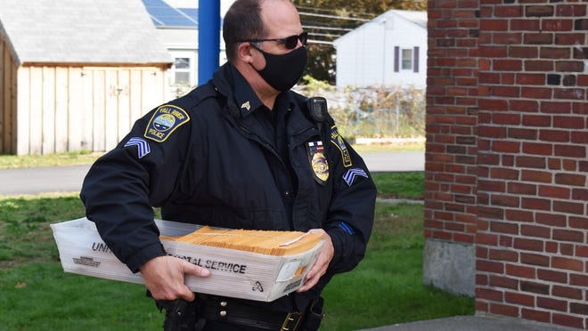 A Fall River police officer delivers ballots to the Calvary Temple Tuesday.