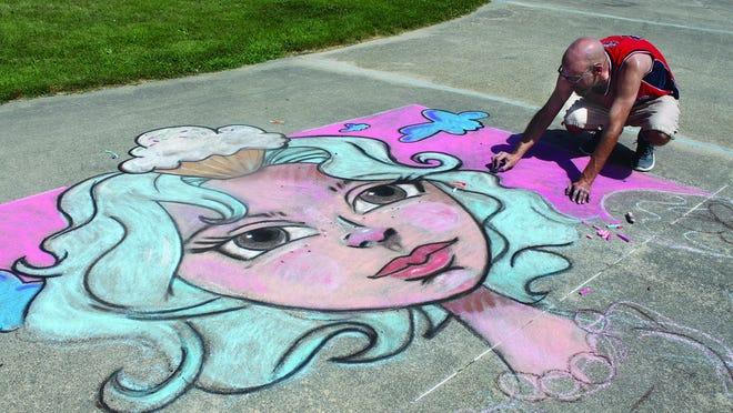 An artist from Iowa works on his chalk entry at the Prairie Chicken Chalk Art Festival.