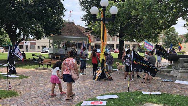 People walk among racial justice displays in Chandler Park Saturday.