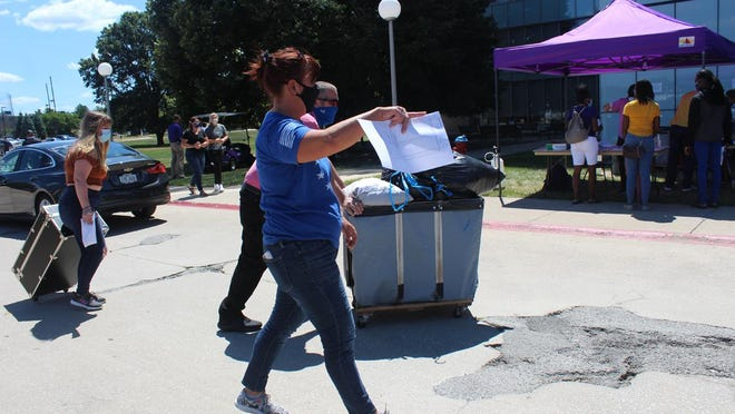 A woman holding a sheet of paper walks parallel to a man pushing a cart towards a Western Illinois University residence hall Wednesday.