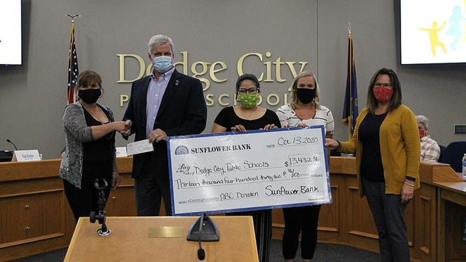 The USD 443 Board of Education accepts a donation of 13,432.86 through Sunflower Bank's ABC Program.