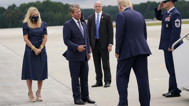 President Donald Trump greets Georgia Gov. Brian Kemp and his wife Marty, left, as he arrives at Dobbins Air Reserve Base for a campaign event at the Cobb Galleria Centre, Friday, Sept. 25, 2020, in Atlanta.
