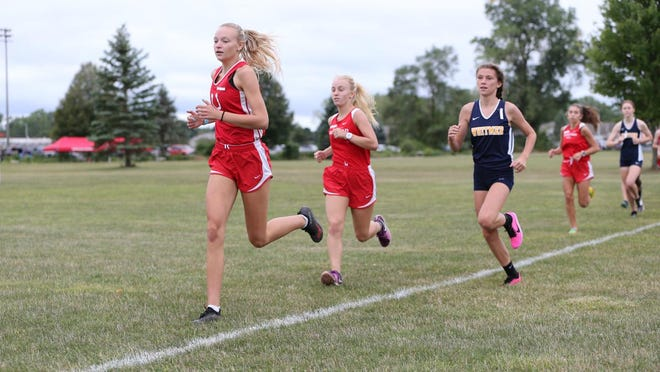 Bedford junior Madison Foster (left) starts to pull from the pack in a dual meet against Whitmer earlier this season.