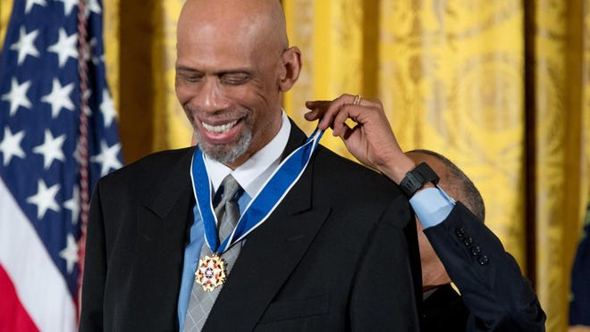 Former NBA basketball player Kareem Abdul Jabbar, left, is presented the Presidential Medal of Freedom by President Barack Obama, right, during a ceremony in the East Room of the White House, Tuesday, Nov. 22, 2016, in Washington. Obama is recognizing 21 Americans with the nation's highest civilian award, including giants of the entertainment industry, sports legends, activists and innovators.