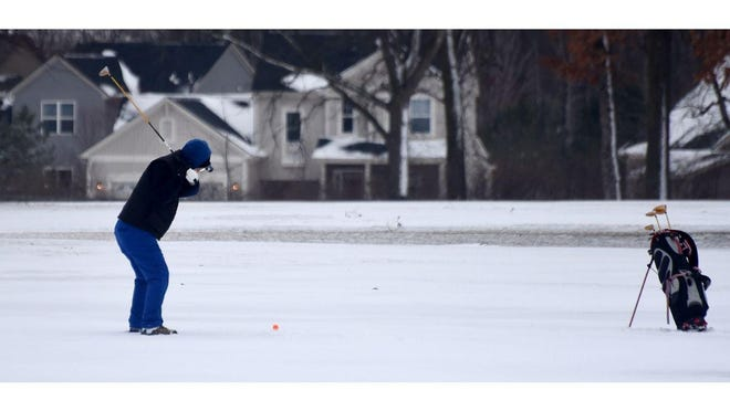 A golfer hits a shot in the snow at Dundee Golf Course Sunday.