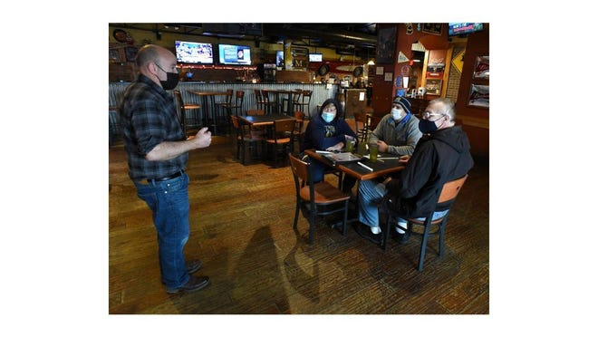 Shane Held, owner of Mugsy's Sports Grille and Bar in Monroe, talks with Jayce Diehl (from left), Daniel Diehl and David Diehl on Monday. They were the restaurant's first customers since a state mandate closed restaurants' dining rooms last year. Dine-in service was able to resume Monday morning.