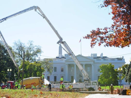 Workers pour cement while installing reviewing stands for the presidential inauguration in front of the White House in Washington, DC on November 12, 2016.