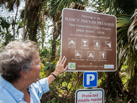 Nancy Payton looks at the sign that displays her name