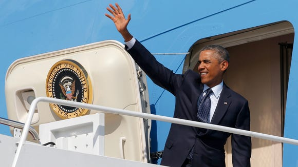 President Barack Obama waves as he boards Air Force