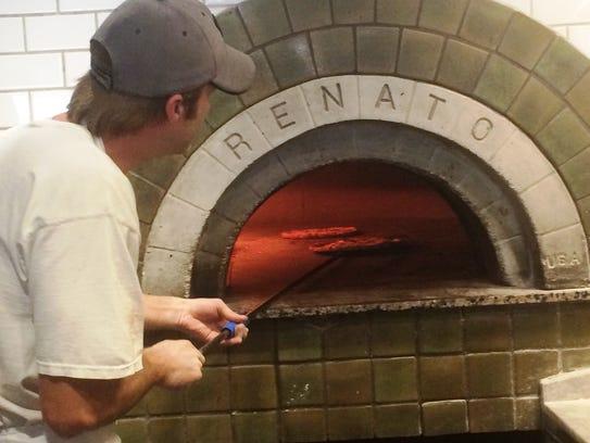 A pizza chef at Il Ritrovo in Sheboygan cooks pizza
