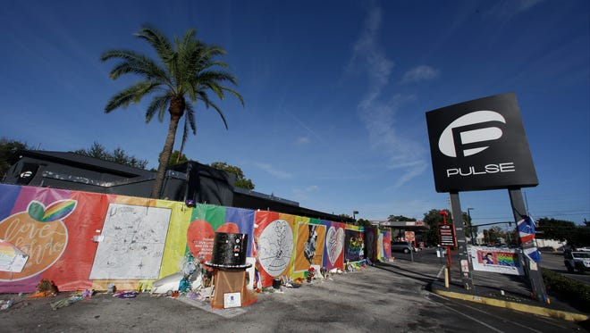 In this Nov. 30, 2016, file photo, artwork and signatures cover a fence around the Pulse nightclub, scene of a mass shooting in Orlando.