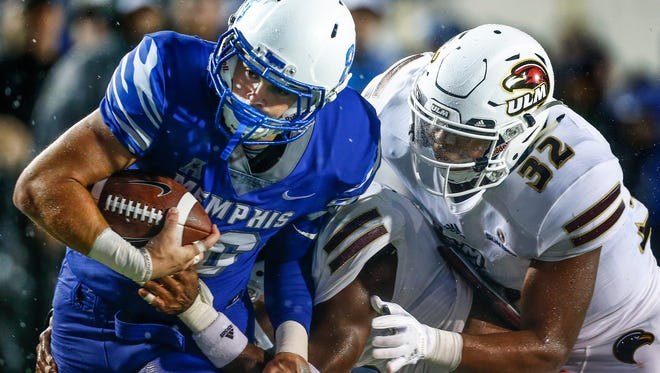 University of Memphis tight end Joey Magnifico (left) fights his way to the one-yard line while dragging  University of Louisiana-Monroe defenders Wesley Thompson (middle) and Chase Day (right) during first quarter action at the Liberty Bowl Memorial Stadium.