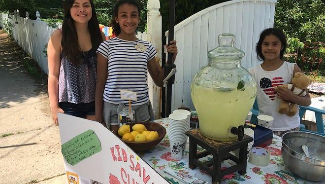 The Egan children, from left, Francy, 18, Arabella, 11, and Angelina, 9, sell lemonade outside their Montclair home to raise money for Kidsave programs.